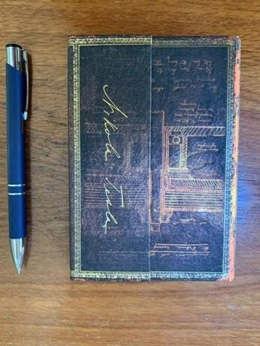 A photo of a blue pen next to a decorated journal.