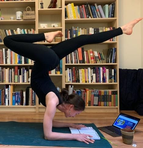 A photo of a woman engaged in a yoga pose with her feet balanced above her head while reading a textbook with a laptop in front of her.