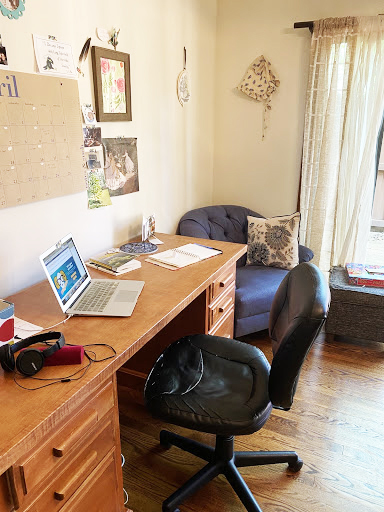 A photo of the same work from home space from a slightly different angle, complete with laptop, computer chair, desk, calendar, and wall hangings.