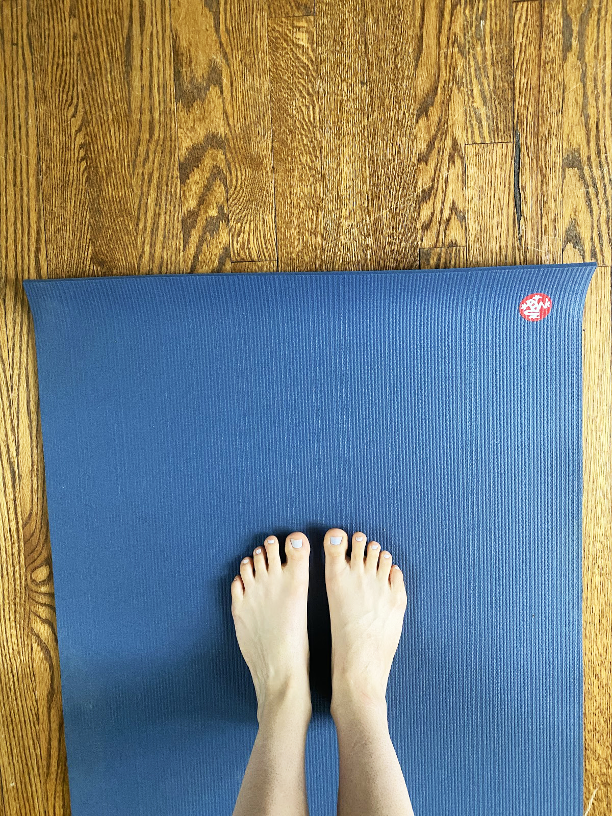 A photo of two feet with pale blue nail polish on a blue yoga mat on a wooden floor.