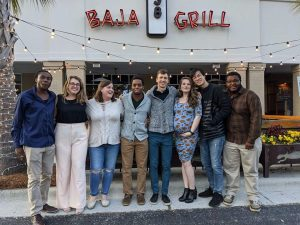 A photo of a group of smiling people outside of Baja Grill to emphasize gatherings before Covid-19.