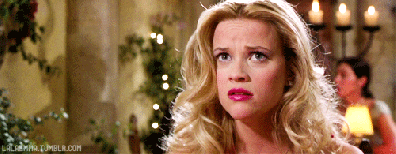 A still frame of Elle Woods from the film Legally Blonde with curled, styled hair looking toward the camera with a worried expression.