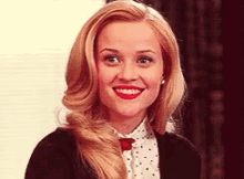 A still frame of Elle Woods from the film Legally Blonde smiling widely in a prim outfit.
