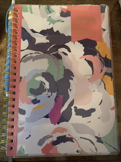 A photo of a planner with an abstract paint stroke cover.