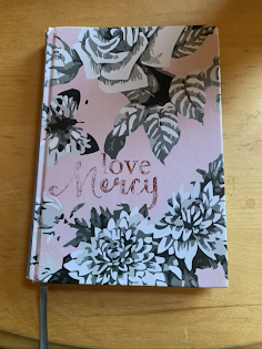 A photo of the cover of a pink notebook with black and white flowers on it.