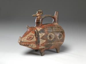 A bottle in the form of a pig for comparison with an oil painting of two pigs with piglets in a sty.