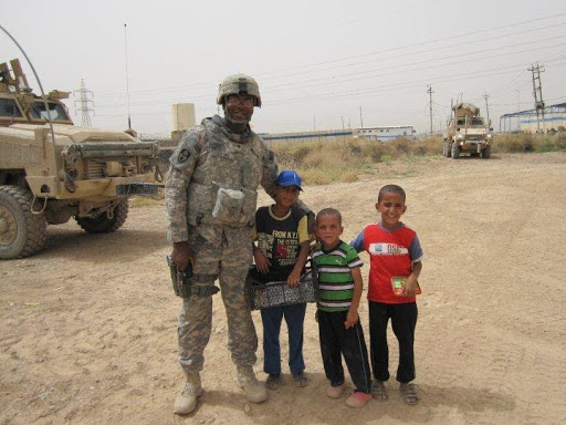 The author, wearing in his army uniform, embraces three Iraqi children selling peanuts.