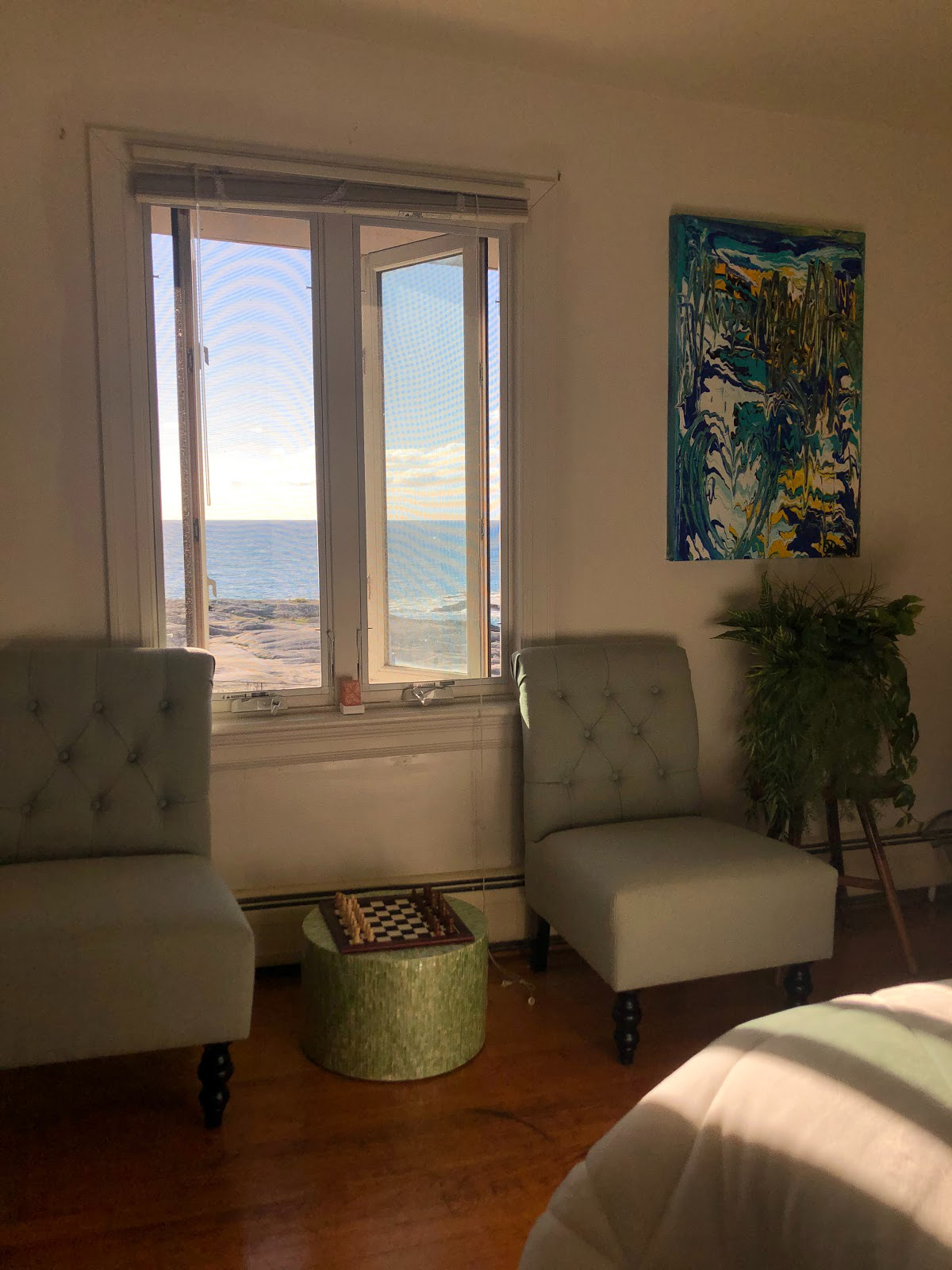 Two chairs are pictured that are right next to a window overlooking the ocean.