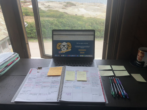 A planner sits on top of a desk with neatly-organized pens and four sticky notes to the right of the planner. The desk sits in front of a window that overlooks the water.