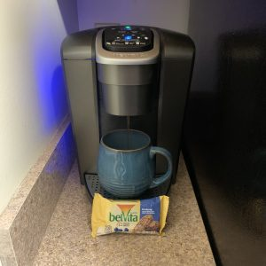 Coffee drips from a Keurig into a blue mug.