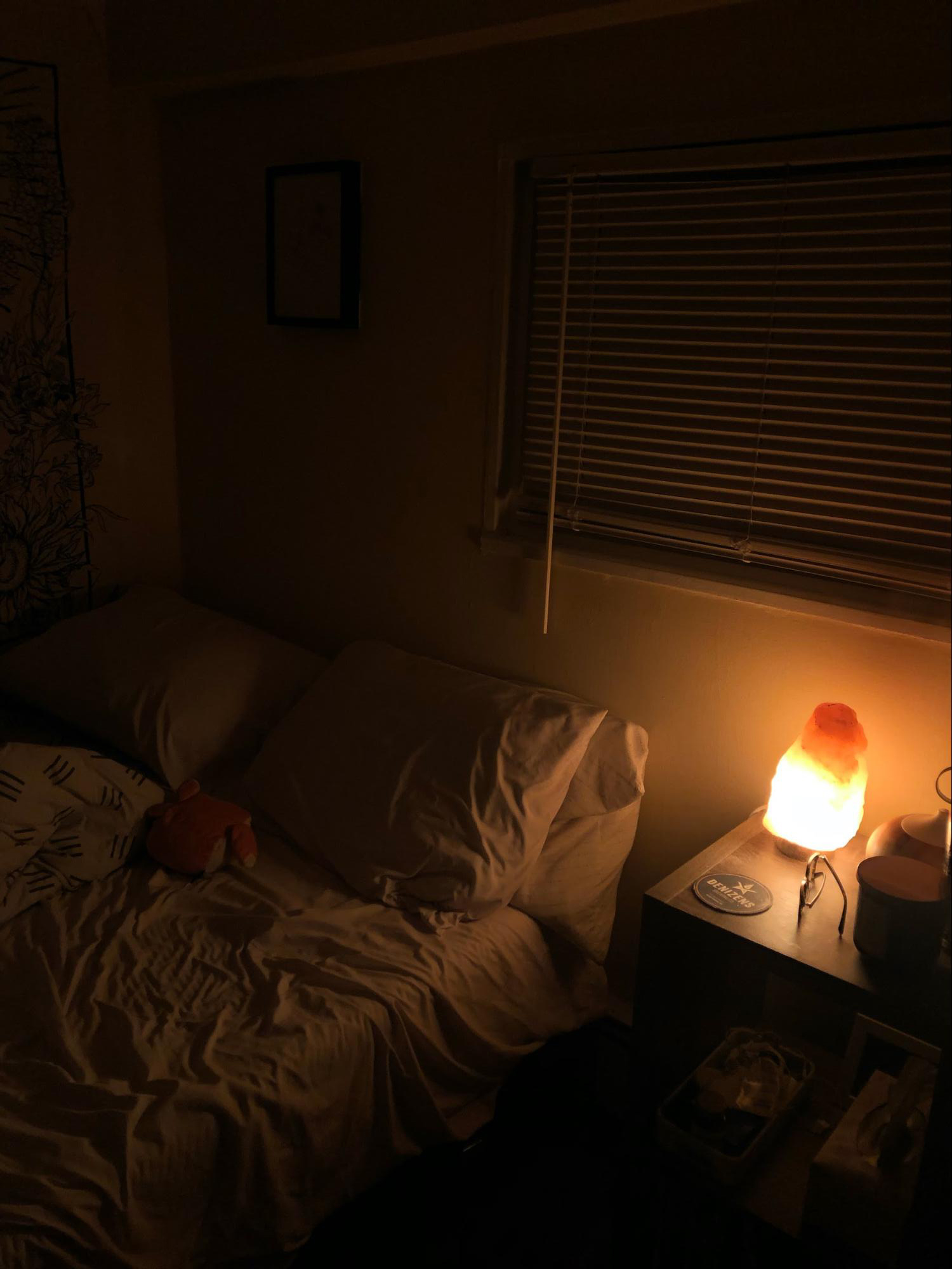 A salt lamp on the night stand dimly lights the dark bedroom and an essential oil diffuser is plugged in on the night stand.