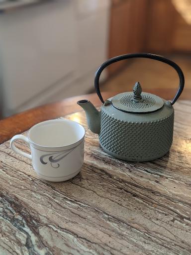A  cup of tea and a ceramic tea pot on top of a table.