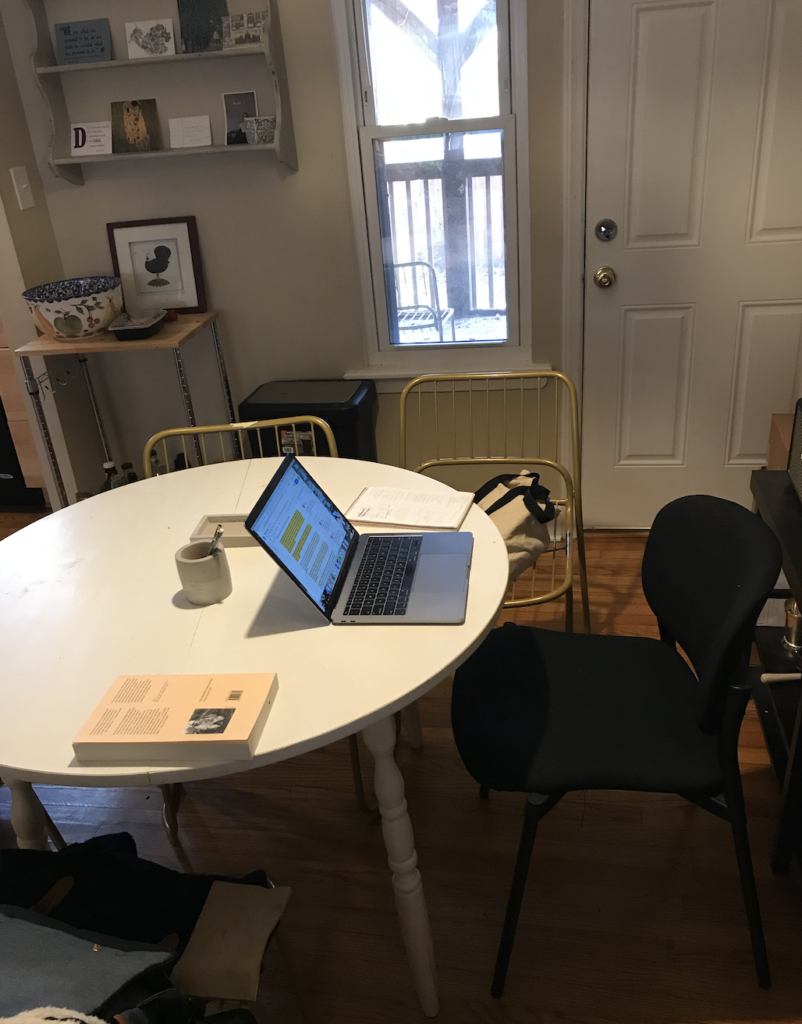 An open laptop, notebook, book, and mug sit on top of an empty table by the front door.