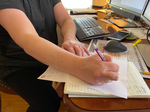 A person sits in front of a computer screen, looking down at a piece of paper with a pencil in hand.
