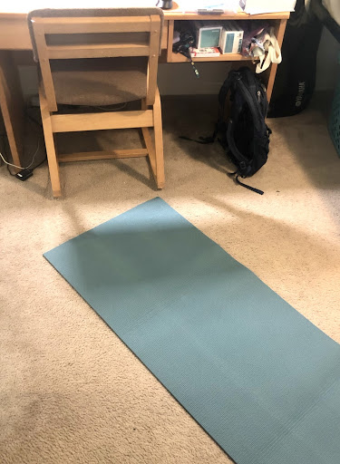 A yoga mat laid out on the floor behind a desk.